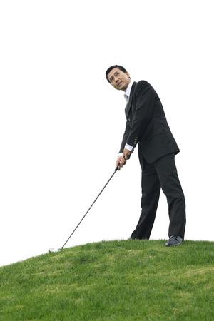 Businessman preparing to drive golf ball photo