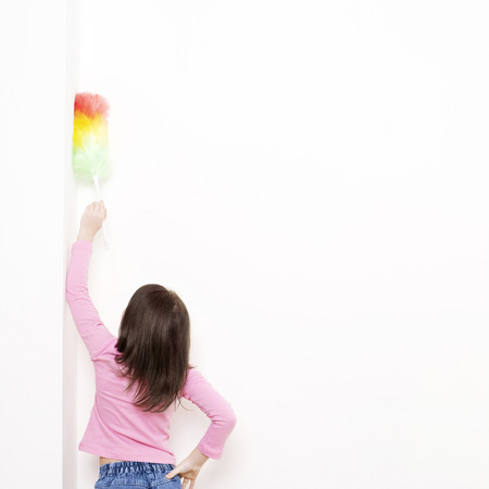 dusting: Girl dusting the wall with a feather duster