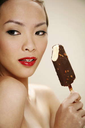 Young woman enjoying a stick of chocolate ice-cream photo