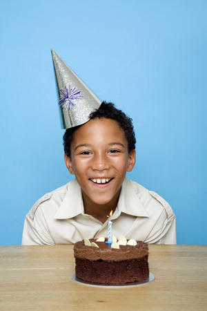 Boy posing in front of his birthday cake photo