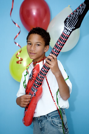 Boy playing with an inflatable guitar photo