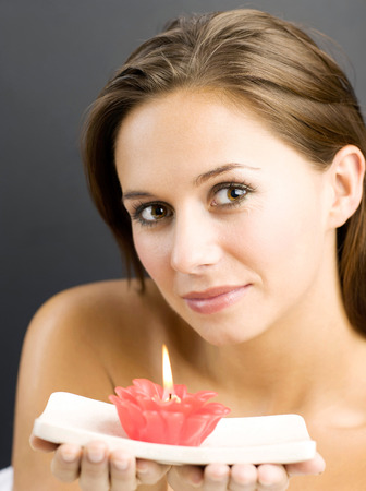 Woman holding a lighted aromatherapy candle Stock Photo - 26264472
