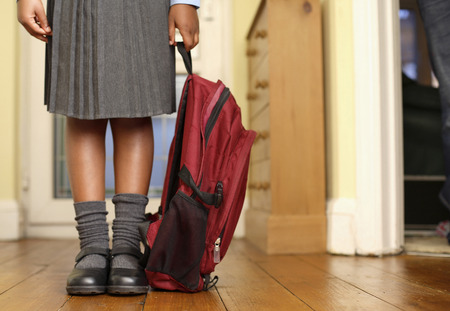 Girl in school uniform holding school bag Stock Photo