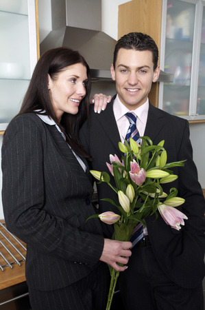 Couple in working attire with a bouquet of flowers photo