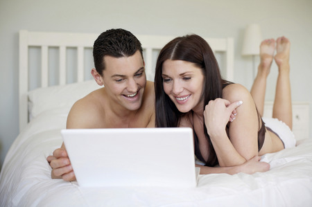 lying forward: Couple lying forward on the bed using laptop Stock Photo