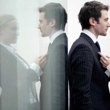 Businesswoman holding businessmans suit photo