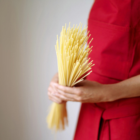 Side view of a lady in red apron holding some spaghetti photo