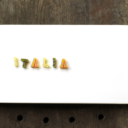 Some alphabet pasta being arranged into a word photo