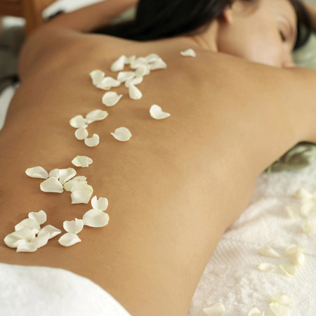 Woman lying on a massage table with rose petals on her back photo