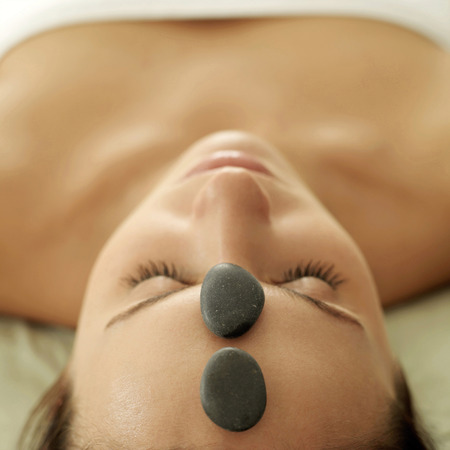 Woman receiving hot stone treatment photo