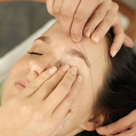 threading hair: Hand using thread to remove facial hair from womans face