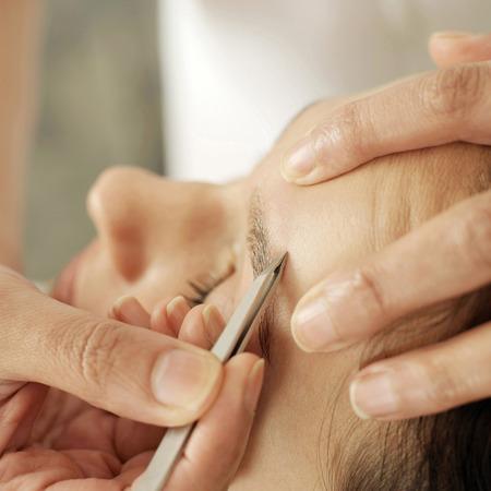 tweezing eyebrow: Hand tweezing womans eyebrow Stock Photo