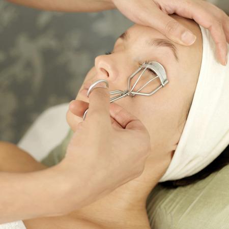 self indulgence: Hand using eyelash curler on a woman