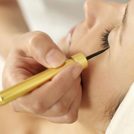 eyelid: Hand applying liquid eyeliner on womans eyelid