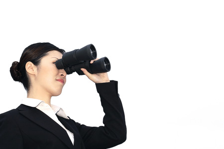 Businesswoman looking through binoculars photo