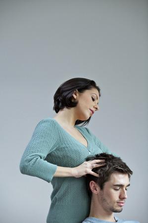 Vrouw die haar vriend een ontspannende hoofdmassage