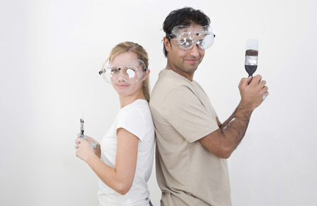 Couple with protection goggles and paint brush posing for the camera photo