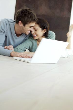 laying forward: Couple using laptop Stock Photo