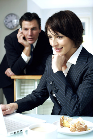 Businesswoman using laptop with her husband talking on the phone in the background photo