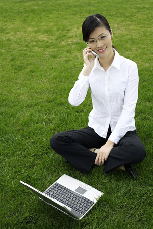 Businesswoman talking on the mobile phone while using laptop photo