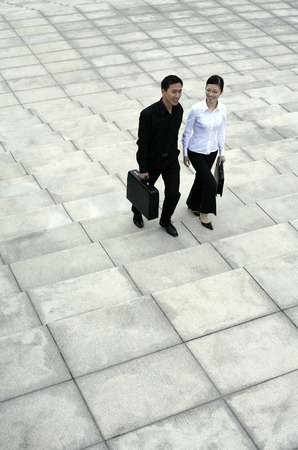 Businessman and businesswoman walking up the stairs photo