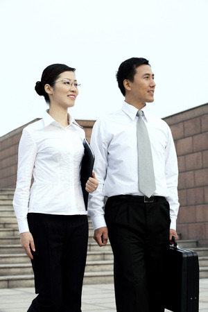 workmate: Businessman and businesswoman walking together Stock Photo