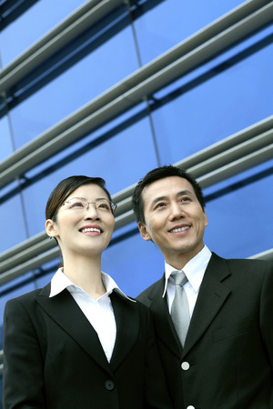 Businesswoman and businessman smiling while looking away photo