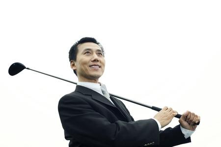 Businessman swinging golf club photo