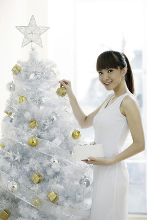 decorating christmas tree: Young woman decorating Christmas tree Stock Photo