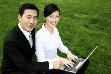 Businessman and businesswoman smiling at the camera while sharing a laptop photo