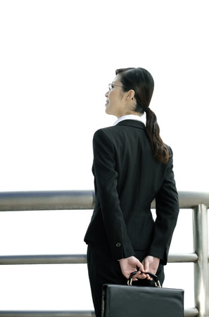 Businesswoman carrying briefcase while looking away photo