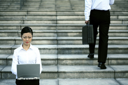 Businesswoman sitting at the staircase using laptop photo