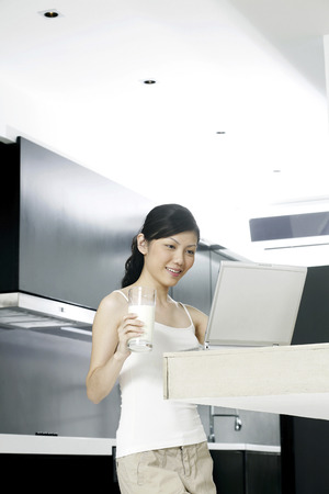 Woman using laptop in the kitchen photo