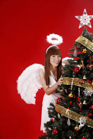 Young woman in angel costume standing beside Christmas tree photo