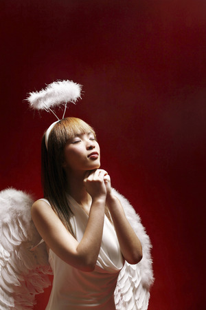 Young woman in angel costume making a wish