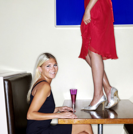 Naughty woman standing on top of table in a bar photo