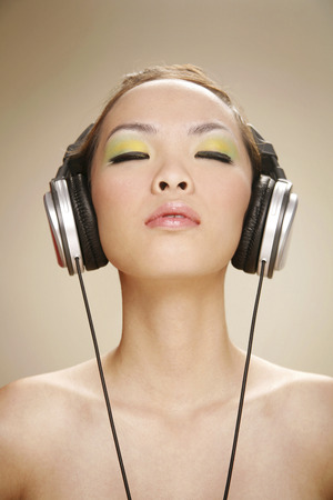 Young woman listening to music on the headphones photo