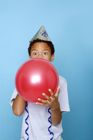 Boy blowing up a balloon photo
