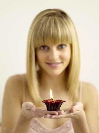 Pretty girl holding a lighted aromatherapy candle Stock Photo - 26266914