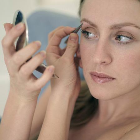 eyebrow trimming: Woman plucking eyebrow Stock Photo