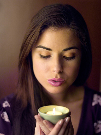 Woman holding a lighted aromatherapy candle Stock Photo