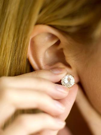 pierced ears: Putting on an earring