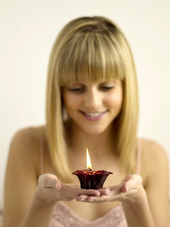 Pretty girl holding a lighted aromatherapy candle Stock Photo - 26267366