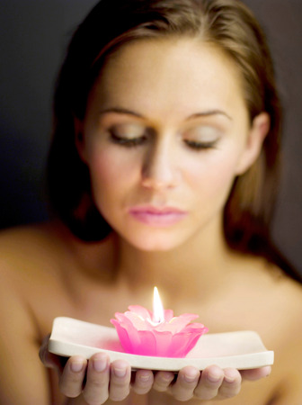 Woman holding a lighted aromatherapy candle Stock Photo - 26267223
