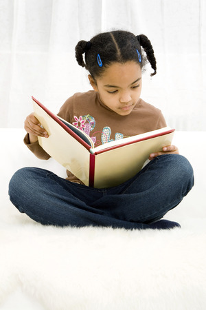 Girl sitting on the bed reading book photo