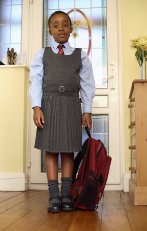 Girl in school uniform holding school bag photo