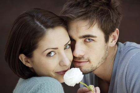 Couple smiling at the camera while holding a white rose photo