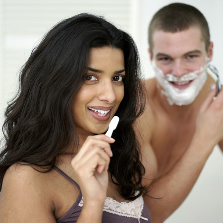 Man shaving his face while his girlfriend is brushing teeth photo