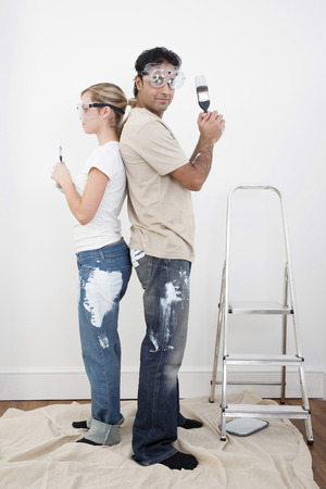 Couple with protection goggles posing with paint brush photo