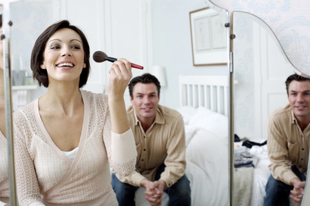 Man watching his wife looking at the mirror applying make-up